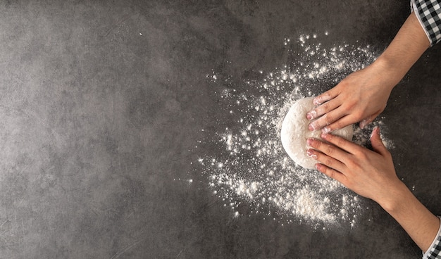 Mains faisant une pâte à pizza avec de la farine sur le fond de béton gris