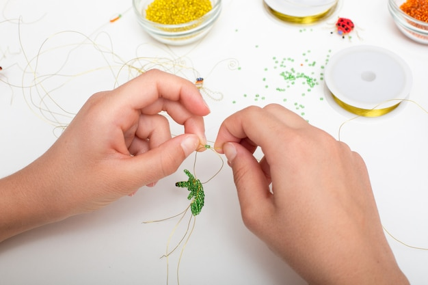 Mains faisant des perles et des bijoux en fil