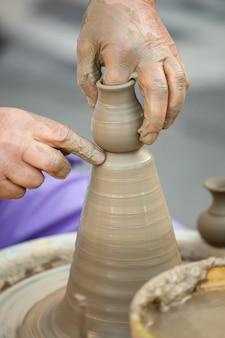 Mains faisant la poterie sur une roue