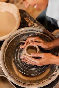Mains faisant de la poterie se bouchent