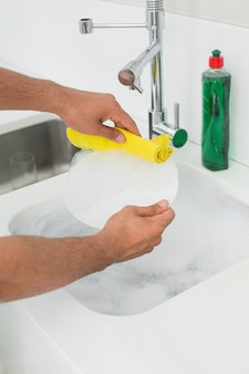 Mains faisant la vaisselle à l'évier