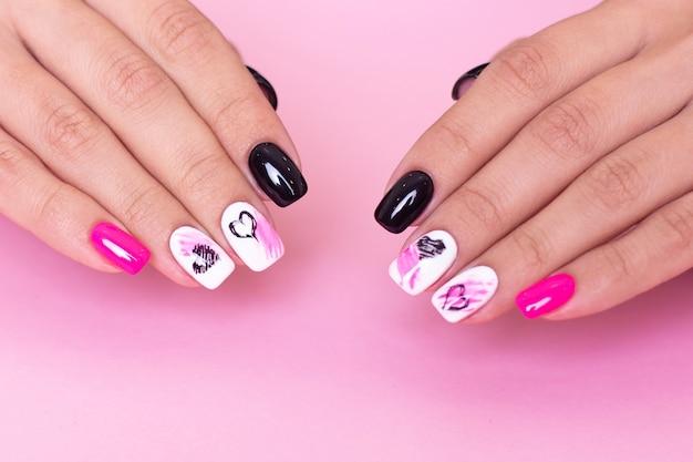 Mains femelles avec la conception de coeurs d'ongles de manucure de mode sur le fond rose