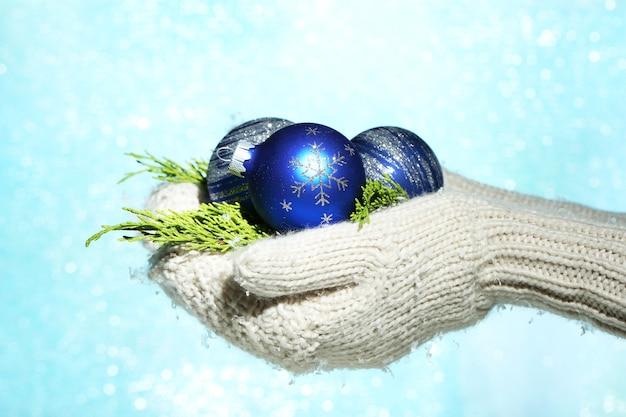 Mains femelles dans des boules d'arbre de noël de mitaines, sur le fond de couleur