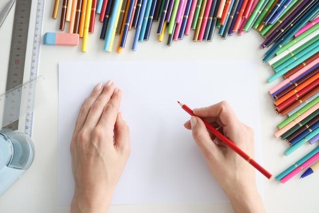 Mains femelles dessinant sur le papier avec le plan rapproché coloré de crayons