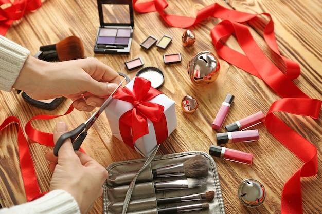 Mains femelles enveloppant le cadeau de noël et le cosmétique coloré de maquillage sur le fond en bois