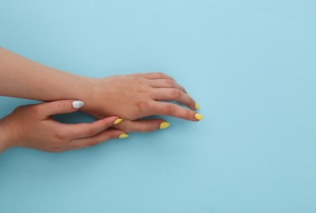 Mains femelles avec une manucure jaune sur un bleu