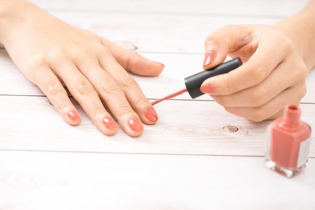 Mains femelles avec la manucure rouge et une bouteille ouverte de vernis sur la table