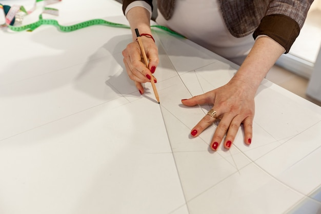 Mains femelles marquant un modèle sur une table blanche