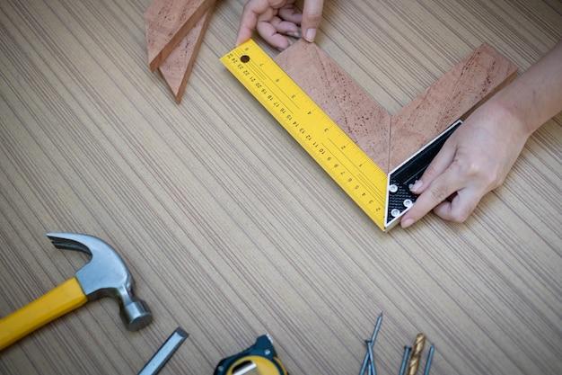 Mains féminines à l'aide d'un carré d'essai pour vérifier que les coins du bois sont carrés avec un ensemble d'outils à main de travail pour le bois, ensemble d'outils avec le faire vous-même (bricolage)