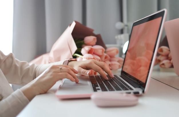 Mains féminines à l'aide d'un ordinateur portable. bureau féminin espace de travail bureau à domicile maquette avec ordinateur portable, bouquet de fleurs de tulipes roses, smartphone et accessoires roses.