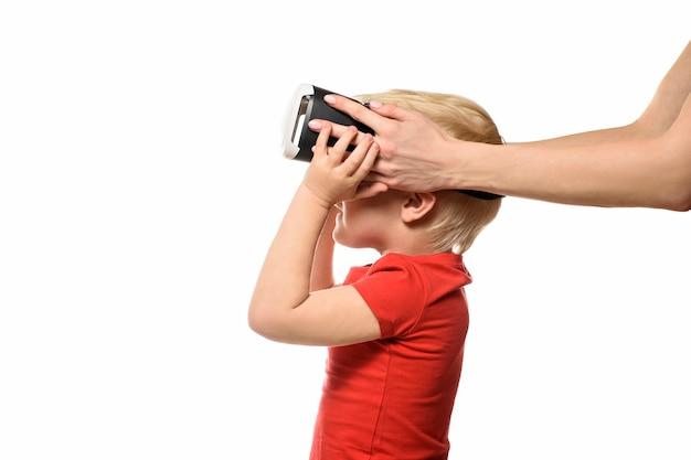 Des mains féminines aident un petit garçon en t-shirt rouge à l'expérience de la réalité virtuelle. isoler sur fond blanc. concept technologique.