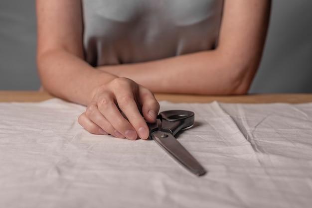 Mains féminines allongées sur des ciseaux en métal sur un tissu naturel concept de couture à la maison comme passe-temps à la mode