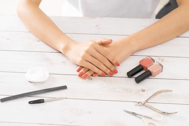 Mains féminines appliquant du vernis à ongles violet sur une table en bois avec une serviette et un ensemble d'ongles