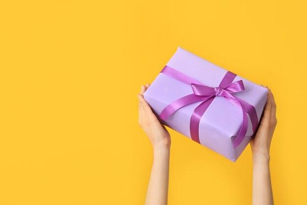 Mains féminines avec une belle boîte-cadeau sur fond de couleur
