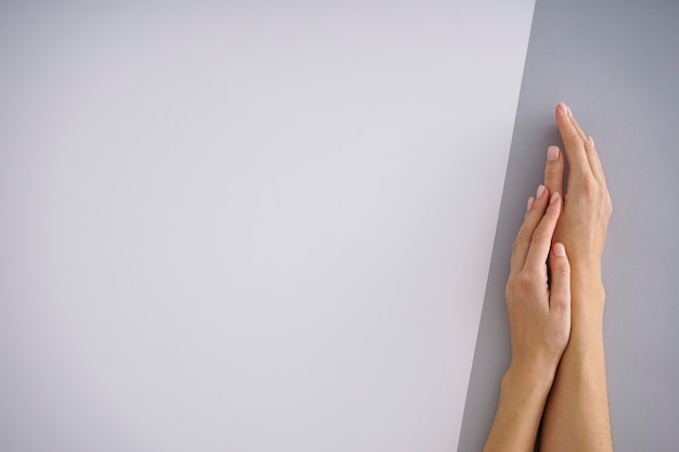 Mains féminines avec une belle manucure sur fond blanc-gris. place pour le texte.