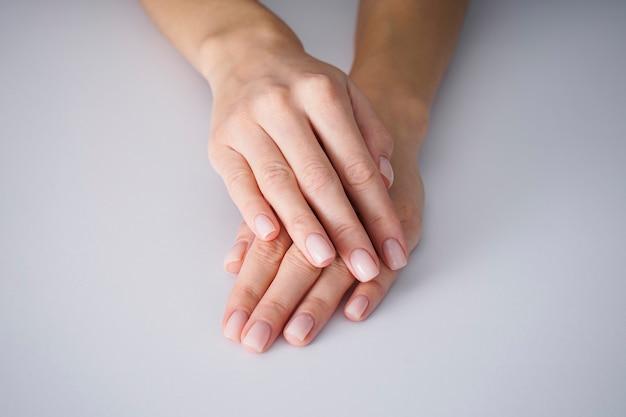 Mains féminines avec une belle manucure sur fond gris, nues.