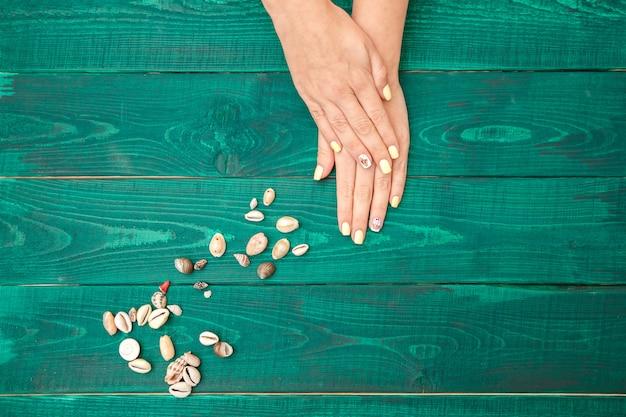 Mains féminines avec une belle manucure sur fond vert. la vue d'en haut