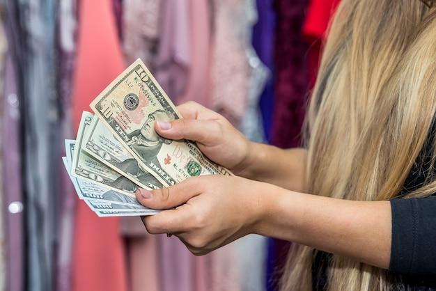 Mains féminines avec des billets en dollars sur fond coloré