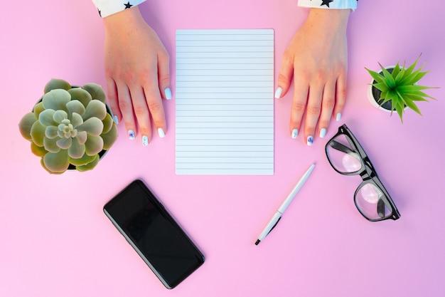 Mains féminines et bloc-notes ouvert sur rose