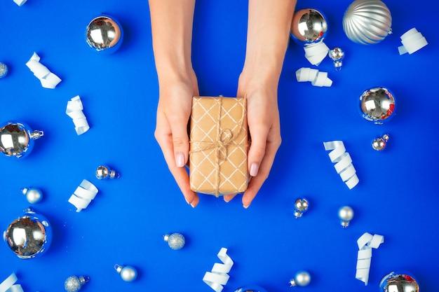 Mains féminines avec boîte-cadeau sur un bleu
