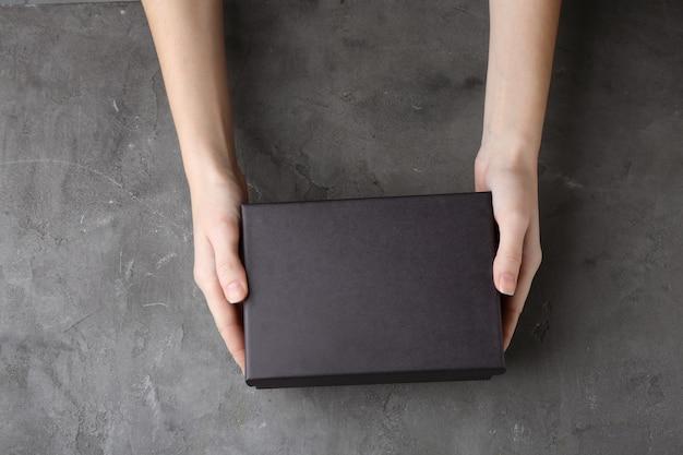 Mains féminines avec boîte noire sur fond texturé gris
