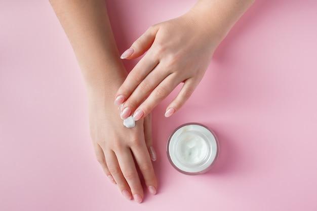 Mains féminines avec une bouteille de crème sur fond rose concept de spa et de soins du corps