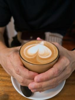 Mains féminines avec café de verre sur la table.