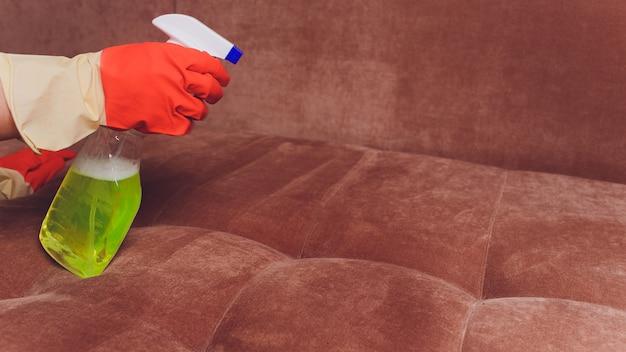 Mains féminines avec un canapé de nettoyage par pulvérisation