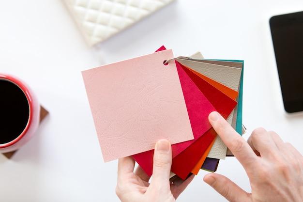Les mains féminines choisissant un motif de tissu de couleur