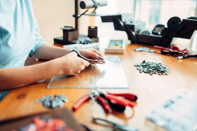 Mains féminines avec des ciseaux, vue de dessus, travaux d'aiguille