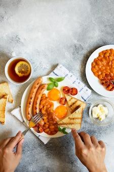 Mains féminines comme elle prend un petit déjeuner anglais avec des saucisses frites, des haricots, des champignons, des œufs frits, des tomates grillées. servi avec une tasse de thé au citron, pain grillé et beurre. fond gris