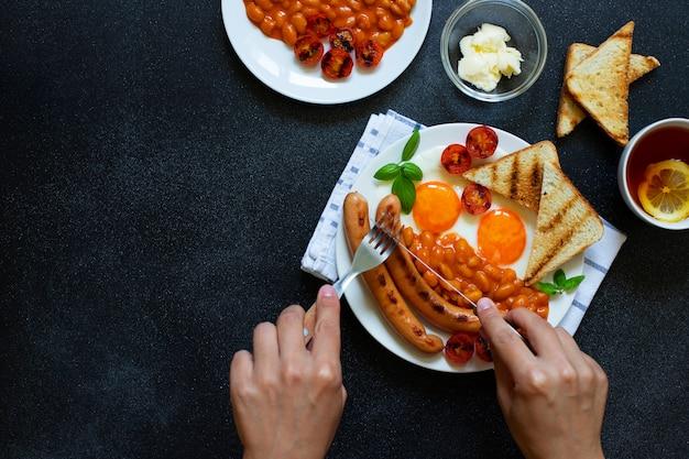 Mains féminines comme elle prend un petit déjeuner anglais avec des saucisses frites, des haricots, des champignons, des œufs frits, des tomates grillées. servi avec une tasse de thé au citron, pain grillé et beurre. fond noir