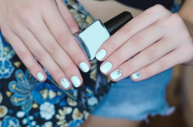 Mains féminines avec la conception des ongles bleu clair
