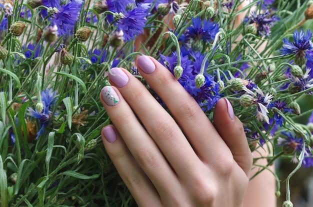 Mains féminines avec la conception des ongles lilas