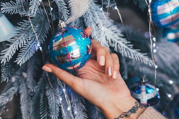 Mains féminines avec la conception des ongles de noël nouvel an. manucure vernis à ongles beige nude, bronze doré brillant à un doigt