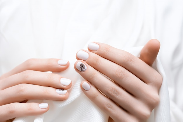 Mains féminines avec la conception des ongles de pissenlit blanc.