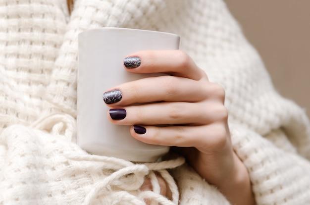 Mains féminines avec la conception des ongles sombres.