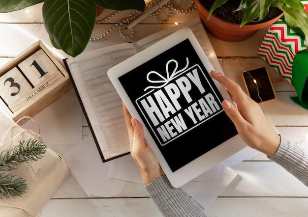 Mains féminines contre une table en bois avec un cadeau tenant une tablette avec des voeux de bonne année et de joyeux noël. concept de noël, nouvel an 2020, humeur hivernale, vacances. copyspace, flyer, carte postale.