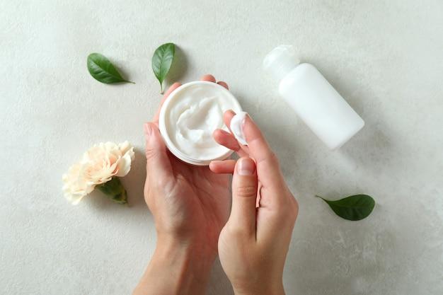 Mains féminines et cosmétiques naturels de spa sur une table texturée blanche