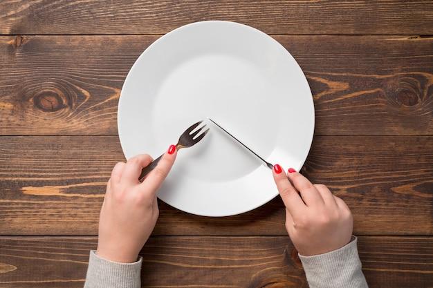 Mains féminines avec couteau et fourchette sur assiette vide blanche