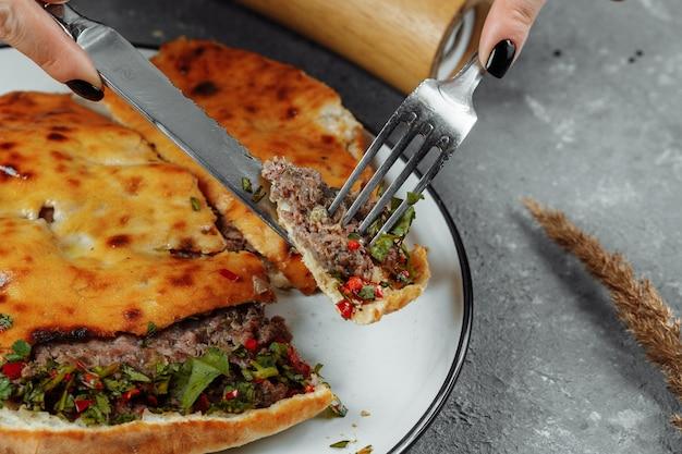 Mains féminines avec un couteau et une fourchette coupées khachapuri avec de l'agneau et du piment