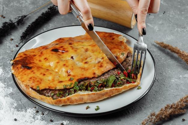 Des mains féminines avec un couteau et une fourchette coupent khachapuri avec de l'agneau et du piment. cuisine nationale géorgienne.