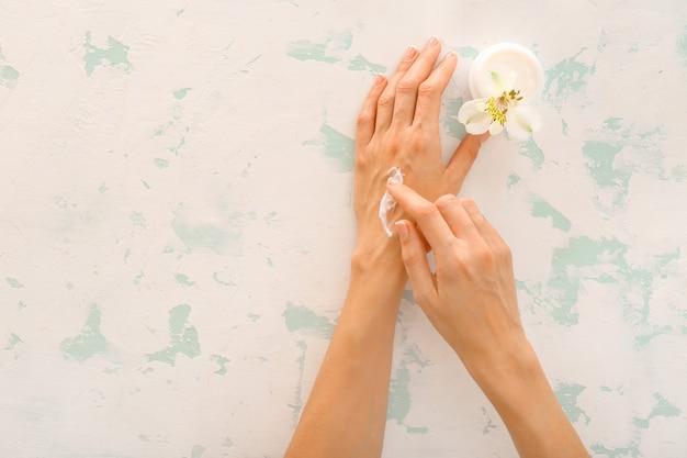 Mains féminines avec crème naturelle sur beige