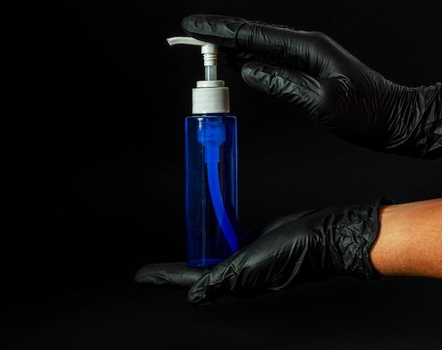 Des mains féminines dans des gants en caoutchouc noir détiennent un pot bleu de savon liquide sur une surface noire