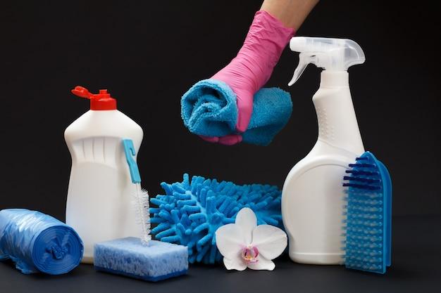 Mains féminines dans des gants en nitrile tenant une fleur d'orchidée près des bouteilles en plastique de liquide de lavage avec un ensemble de nettoyage sur fond noir. ensemble de lavage et de nettoyage.