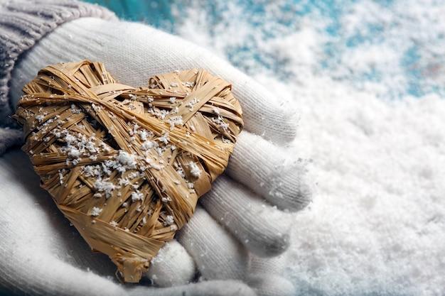 Mains féminines dans des mitaines avec coeur sur la neige
