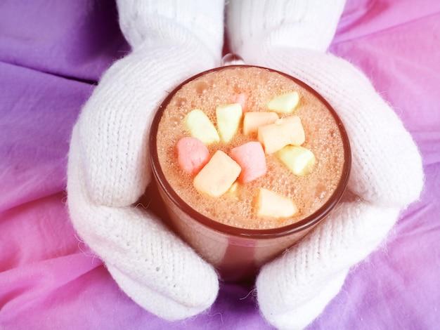 Mains féminines dans des mitaines tenant du chocolat chaud dans une tasse avec des guimauves.