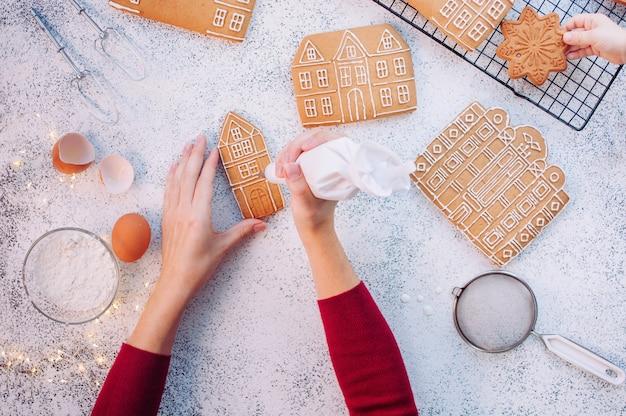 Mains féminines décorant la maison de biscuits de pain d'épice de noël tandis que petit enfant prenant un cookie. vue de dessus, pose à plat.