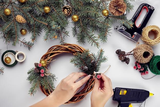 Des mains féminines décorent la couronne de noël avec des branches d'épinette avec des fruits rouges et des cônes de forêt qui...