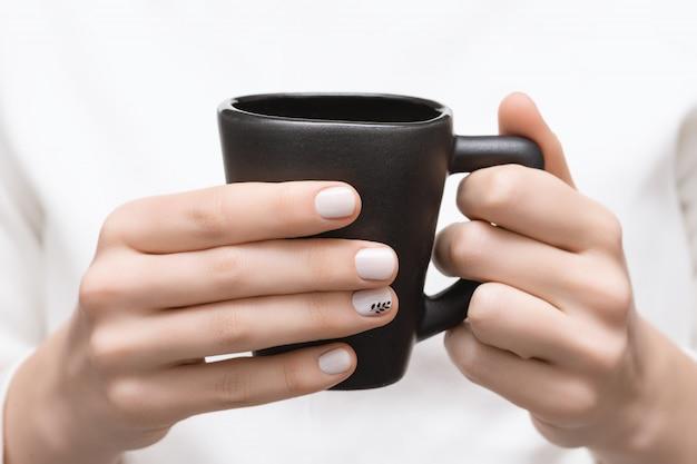 Mains féminines avec un design d'ongle blanc tenant une tasse noire.